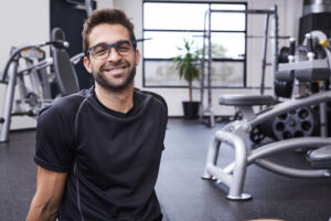 Athletic glasses guy smiling in gym, portrait